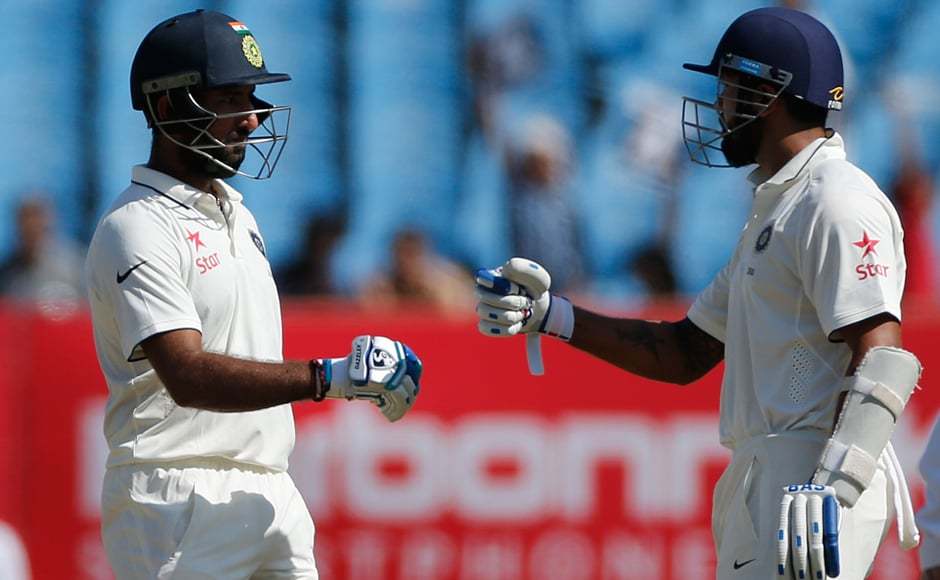Cheteshwar Pujara is congratulated by team mate, Murali Vijay, as he completes a half-century against England. AP
