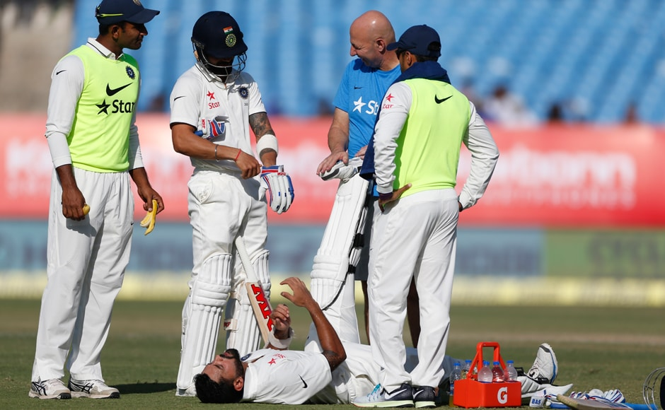 Murali Vijay is attended by team physiotherapist on the third day of the first Test match between India and England in Rajkot. AP