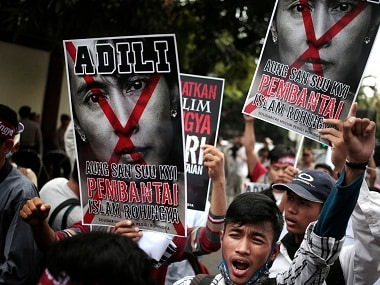 "A Muslim man shouts slogans as he holds a defaced poster of Myanmar's Foreign Minister Aung San Suu Kyi during a rally against the persecution of Rohingya Muslims, outside the Embassy of Myanmar in Jakarta, Indonesia, Friday, Nov. 25, 2016. Persecution of Rohingya in Myanmar has escalated in the past several years and they face violence instigated by Buddhist hard-liners and institutionalized discrimination. Writings on the posters read ""Put Aung San Suu Kyi, the butcher of Rohingya Muslims, to Justice."" (AP Photo/Dita Alangkara)"
