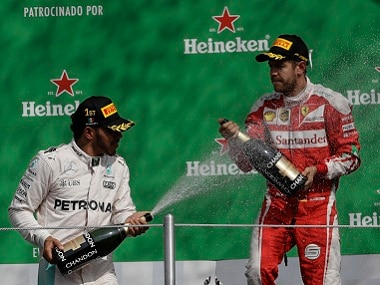 Lewis Hamilton of Mercedes celebrates with Ferrari's Sebastian Vettel after winning the Mexican Grand Prix. AP