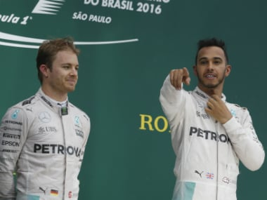 Lewis Hamilton (R) celebrates his victory as Nico Rosberg (L) watches on. AP