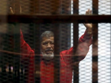 FILE PHOTO: Deposed President Mohamed Mursi greets his lawyers and people from behind bars at a court wearing the red uniform of a prisoner sentenced to death, during his court appearance with Muslim Brotherhood members on the outskirts of Cairo, Egypt, June 21, 2015.  REUTERS/Amr Abdallah Dalsh/File photo - RTX2GWQD