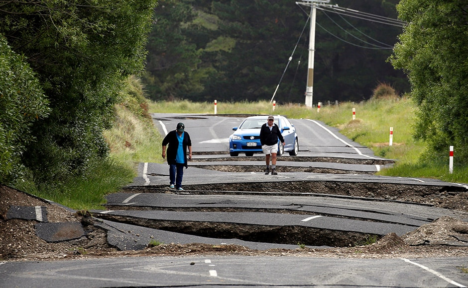 Local residents Chris and Viv Young look at damage caused by an earthquake along State Highway One near the town of Ward, south of Blenheim on New Zealand's South Island, November 14, 2016. REUTERS