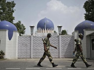 Indian security personnel walk past the main gate of Pakistan High Commission in New Delhi August 19, 2014. India called off on Monday peace talks with Pakistan, giving a jolt to renewed diplomatic efforts between the two nuclear-armed neighbors and adding to the troubles of Pakistan's beleaguered government. REUTERS/Anindito Mukherjee (INDIA - Tags: POLITICS MILITARY)