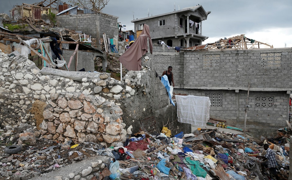 Roughly 90 percent of the piped water supply systems in south-west Haiti were damaged by the storm that struck 4 October, according to Haiti's National Water and Sanitation Directorate. People walk next to destroyed houses in Jeremie. Reuters