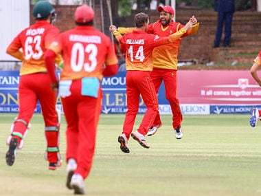 Zimbabwe players celebrate a West Indies wicket. AFP