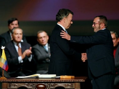 Colombia's President Juan Manuel Santos and Marxist FARC rebel leader Rodrigo Londono, known as Timochenko, shake hands after signing a peace accord in Bogota, Colombia on 24 November. Reuters