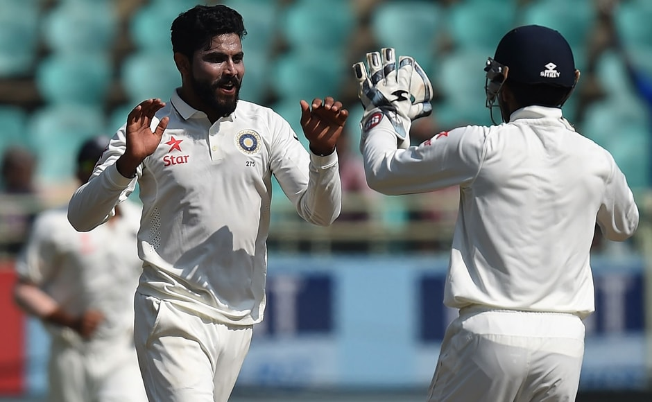 Ravindra Jadeja (L) celebrates the wicket of Moeen Ali with wicketkeeper Wriddhiman Saha during Day 5 of the second Test between India and England at Vishakhapatnam. AFP