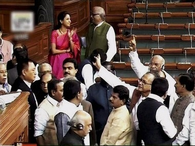 Opposition members protest in the well of Lok Sabha during the winter session of Parliament in New Delhi on Monday. PTI