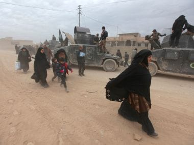 Displaced people walk past Iraqi security forces. Reuters