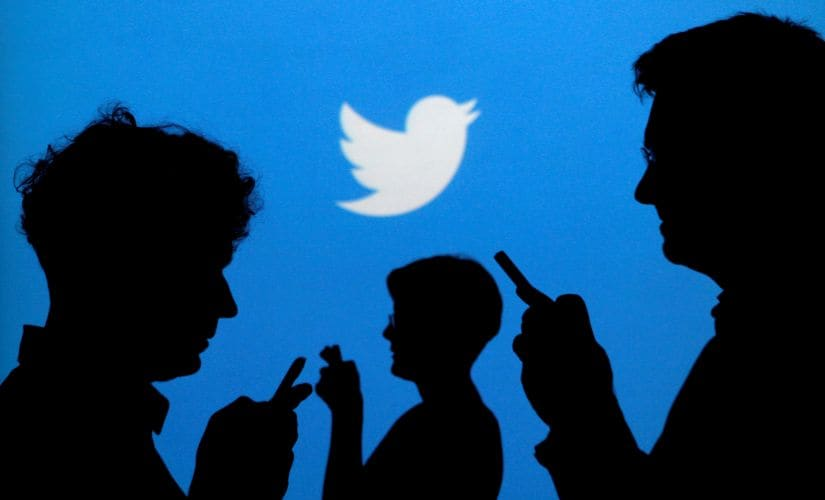 FILE PHOTO: People holding mobile phones are silhouetted against a backdrop projected with the Twitter logo in this illustration picture taken September 27, 2013. REUTERS/Kacper Pempel/Illustration/File Photo - RTX2QA9X