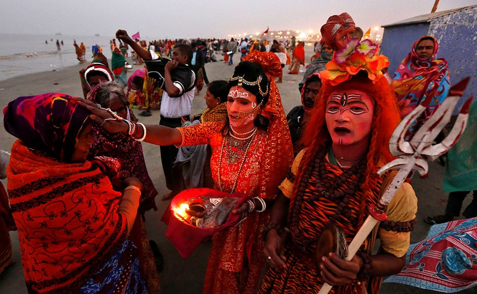 Two men dressed as Hindu Lord Shiva (R) and Goddess Parvati (C) give blessings to a pilgrim at the confluence of the river Ganges and the Bay of Bengal, ahead of the