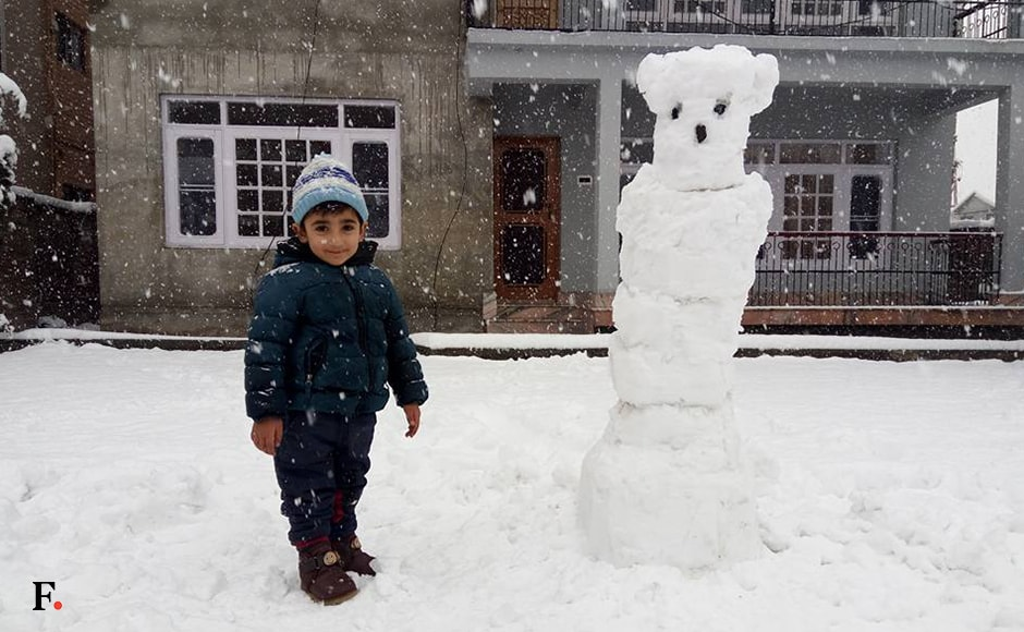 A Kashmiri boy with his snowmen outside his home in Srinagar, making snowmen is the favorite pastime of children during winters. The MET Office has forecast widespread snowfall or rains over the next two days also. Sameer Yasir/Firstpost