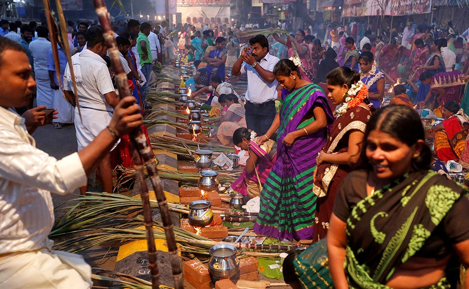 Devotees prepare rice dishes to offer to the Hindu Sun God as they attend Pongal celebrations early morning in Mumbai, India, January 14, 2017. REUTERS/Shailesh Andrade