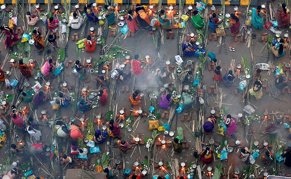 Devotees prepare rice dishes to offer to the Hindu Sun God as they attend Pongal celebrations early morning in Mumbai on 14 January, 2017. Reuters