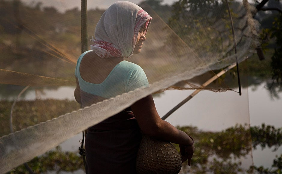 A tribal woman waits with her fishing net to participate in community fishing as part of Bhogali Bihu celebrations in Panbari village, some 50 km east of Guwahati on 13 January, 2017.
