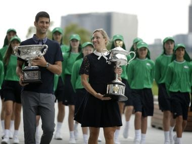 Australian Open defending men's and woman's champions Serbia's Novak Djokovic, left, and Germany's Angelique Kerber carry their trophies. AP