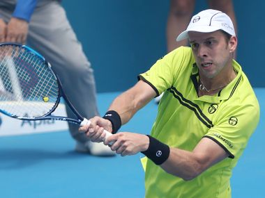 Gilles Muller hits a return to Pablo Cuevas of Uruguay in their quarter-final at the Sydney International. AFP