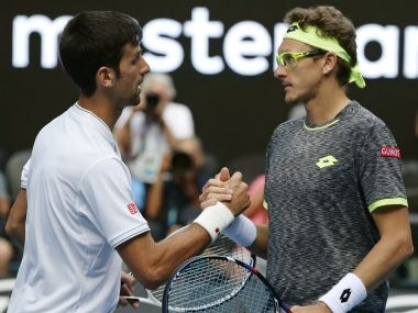 Denis Istomin, right, is congratulated by Novak Djokovic after winning their second round match at the Australian Open. AP