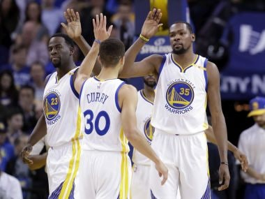 Golden State Warriors' Kevin Durant celebrates with teammate Stephen Curry. AP
