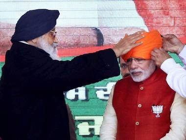 Punjab Chief Minister Parkash Singh Bada ties a turban for Prime Minister Narendra Modi in Jalandhar on Friday. PTI