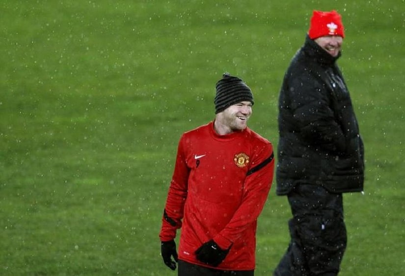Manchester United manager Alex Ferguson and Wayne Rooney (L) smile during a team training session in Basel December 6, 2011. Manchester United will face FC Basel (FCB) in their Champions League Group C soccer match on Wednesday in Basel.  REUTERS/Arnd Wiegmann (SWITZERLAND - Tags: SPORT SOCCER)