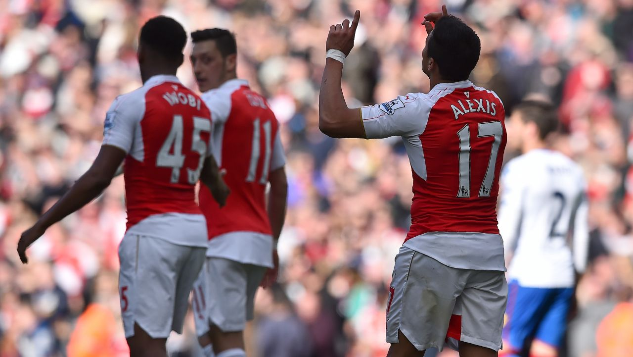 Arsenal's Chilean striker Alexis Sanchez (R) celebrates scoring his team's first goal during the English Premier League football match between Arsenal and Crystal Palace at the Emirates Stadium in London on April 17, 2016. / AFP PHOTO / BEN STANSALL / RESTRICTED TO EDITORIAL USE. No use with unauthorized audio, video, data, fixture lists, club/league logos or 'live' services. Online in-match use limited to 75 images, no video emulation. No use in betting, games or single club/league/player publications. /