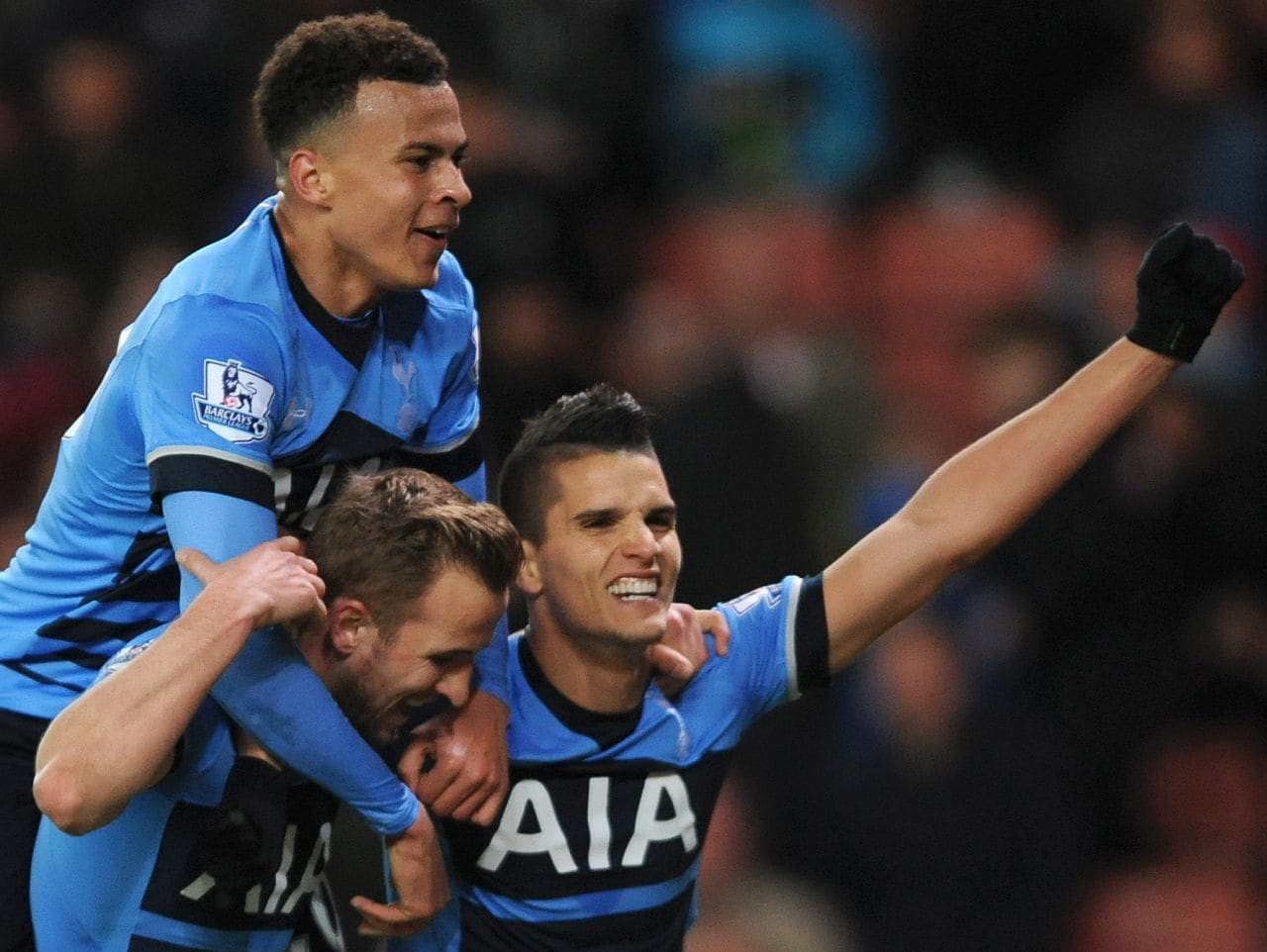 Tottenham's Harry Kane, bottom left, celebrates scoring a goal with Dele Alli, top, and Erik Lamela during the English Premier League soccer match between Stoke City and Tottenham Hotspur at the Britannia Stadium, Stoke on Trent, England, Monday, April 18, 2016. (AP Photo/Rui Vieira)