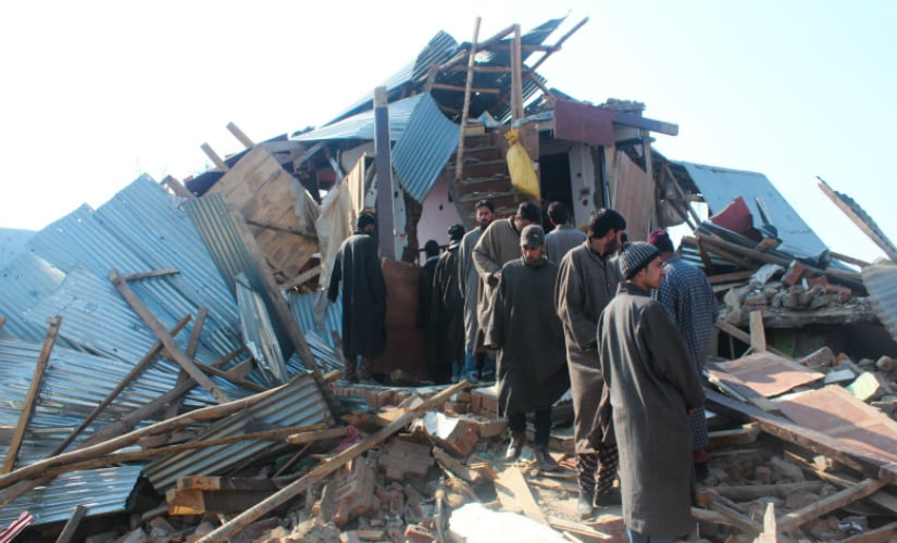 People standing near the debris of a demolished house wherein three top Lashkar-e-Taiba militants were killed in a fierce gunbattle with security forces at North Kashmir's Hajin area. Firstpost/Suhail Bhat