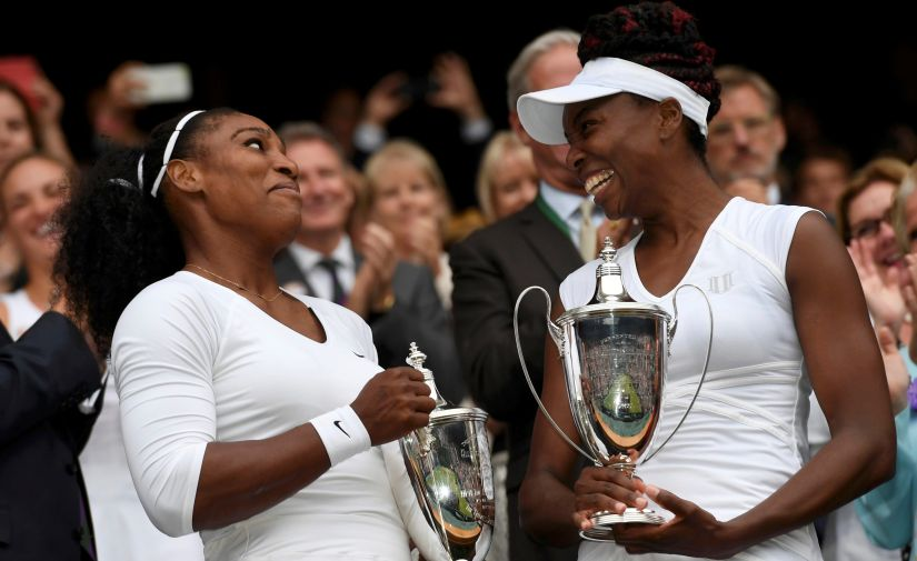 Serena Williams and Venus Williams celebrate winning their womens doubles title at Wimbledon 2016. Reuters