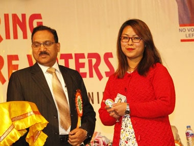 Manipur CEO Vivek Kumar Dewangan distributing Electoral Photo ID Card to a new voter at the City Convention Centre, Imphal on Wednesday. Image courtesy Chief Electoral Officer, Manipur