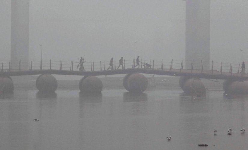 People cross the Pontoon bridge on the river Ganga amid dense fog in Allahabad on Monday. PTI