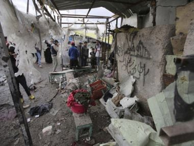 Citizens inspect the scene after a car bomb explosion at a crowded outdoor market in the Iraqi capital's eastern district of Sadr City, Iraq, on Monday. AP