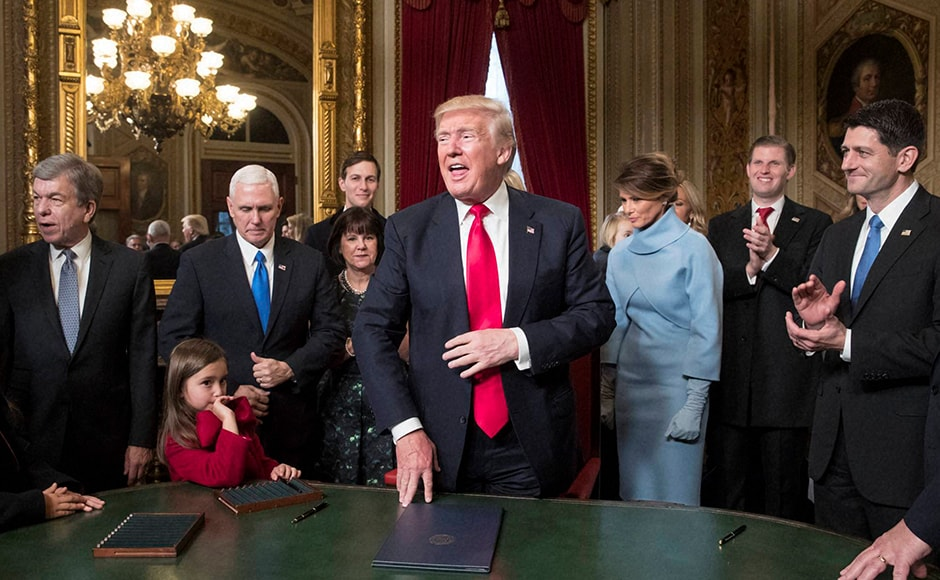 Joining him during the signing, from left, are Sen. Roy Blunt, Vice President Mike Pence and his wife Karen Pence, Jared Kushner, President Trump's wife Melania Trump, Eric Trump, and Speaker of the House Paul Ryan. Donald Trump has taken his first steps in office, signing an executive order aimed at health care reforms. Photo: AP