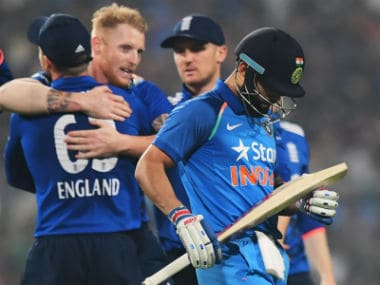 England's Ben Stokes(C) celebrates with teammates at the fall of Virat Kohli's wicket at the Eden Gardens. AFP
