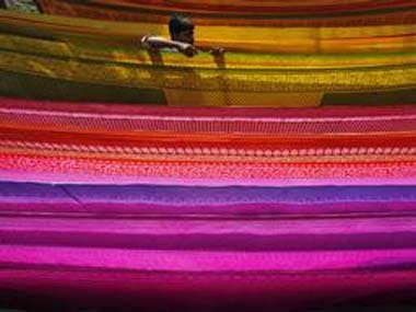 A worker arranges a saree, a traditional cloth used for women's clothing, as it is hung out to dry after dyeing it at a workshop in Shardarpara village, south of Kolkata February 10, 2012. REUTERS/Rupak De Chowdhuri (INDIA - Tags: SOCIETY BUSINESS TEXTILE TPX IMAGES OF THE DAY)