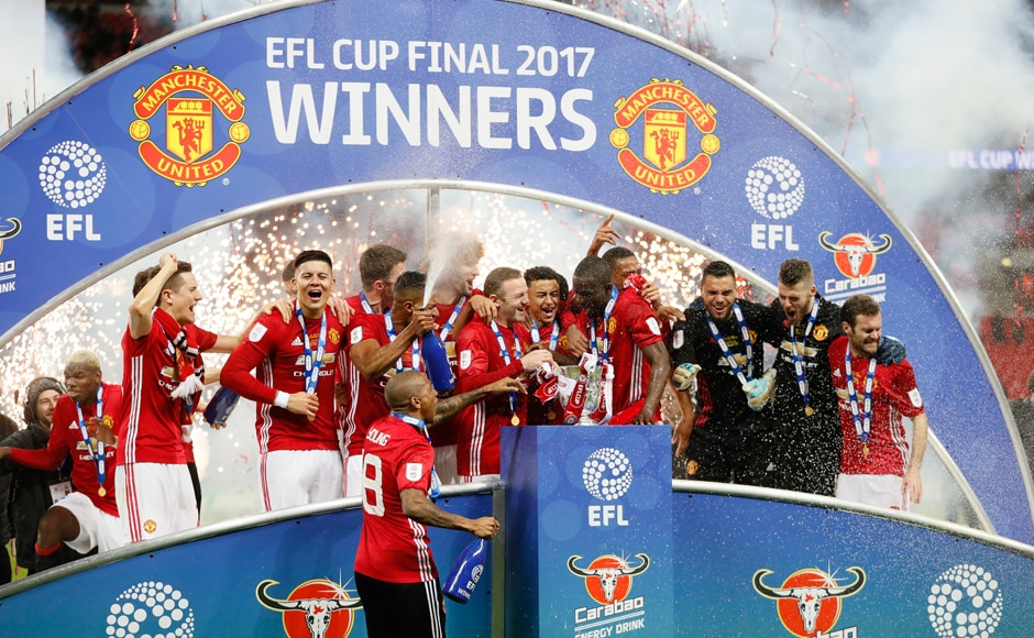 Manchester United players celebrate with the League Cup trophy. Jose Mourinho became the first manager in United history to win a trophy in his first season. AP