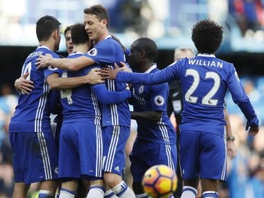 Chelsea's Cesc Fabregas is mobbed by his teammates after scoring against Arsenal. AP