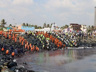 Coast Guard, State revenue personnel, local volunteers, and fishermen removing black oil washed ashore after an LPG tanker collided near Kamarajar Port in Ennore, Chennai. PTI