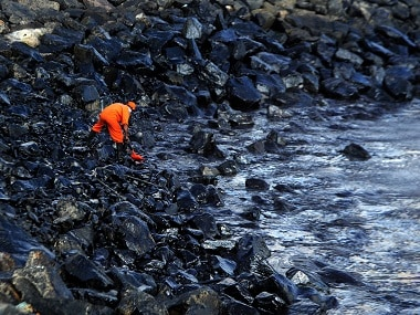 A member of the Pollution Response Team collects a sample of an oil spill from boulders at the coast, a day after an oil tanker and an LPG tanker collided off Kamarajar Port in Ennore, Chennai. AFP
