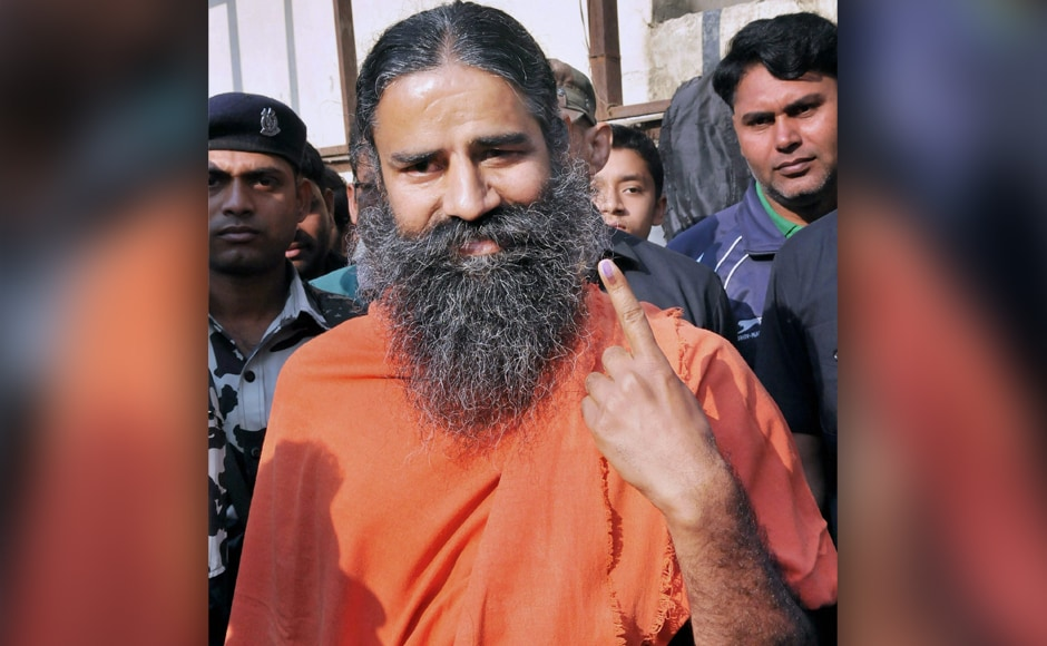 Yoga guru Baba Ramdev shows his inked finger after casting his vote during the Uttarakhand Assembly poll in Haridwar on Wednesday. PTI