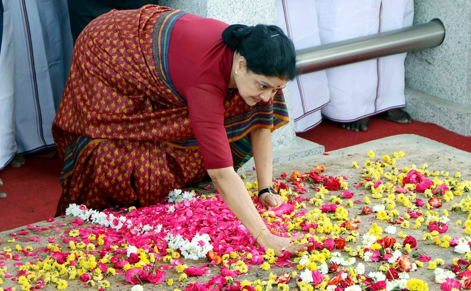 """AIADMK General Secretary VK Sasikala slams her palm at Jayalalithaa's shrine at Marina beach in Chennai taking a mighty vow, saying, """"I will overcome the hurdles, treachery and plotting against me""""', before leaving for Bengaluru to appear in front of a court on Wednesday. PTI"""