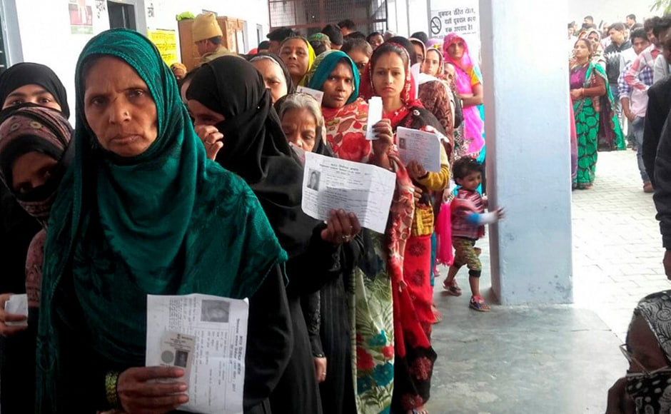 Voters queue up at a polling station to cast their votes during the third phase of UP Assembly elections in Farrukhabad on Sunday. PTI