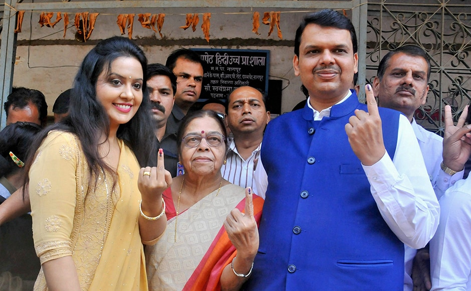 Maharashtra chief minister Devendra Fadnavis along with mother (C) and wife Amruta (L) show their ink-marked fingers after casting their vote during the Municipal election in Nagpur of Maharashtra on Tuesday. PTI