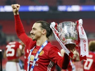 Manchester United's Zlatan Ibrahimovic celebrate with the trophy. AP