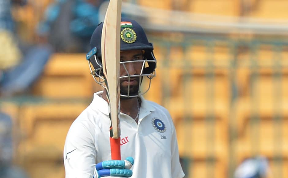 India's Cheteshwar Pujara raises his bat after scoring an invaluable 50 when the team was in deep trouble on Day 3 of the second Test in Bengaluru. AFP