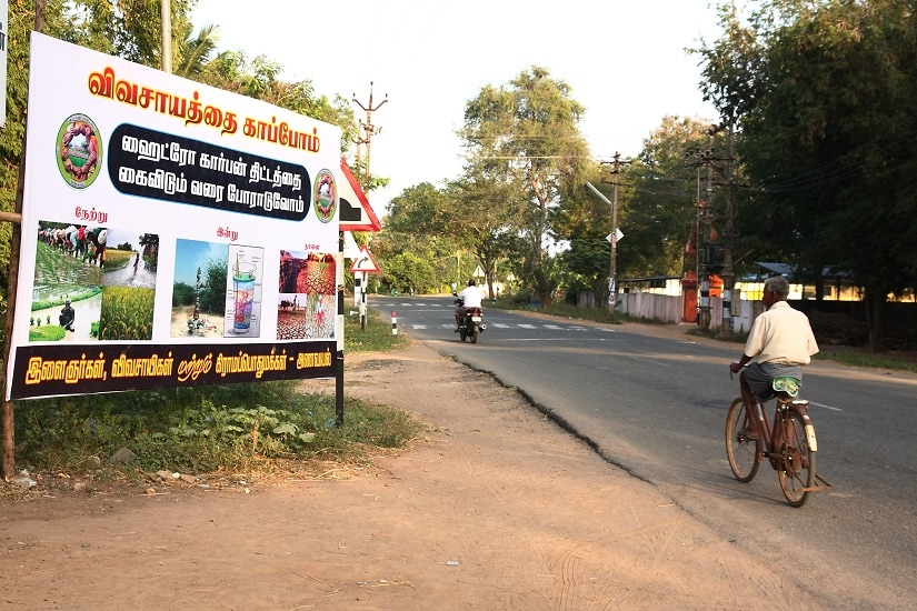 A man cycles past a banner that shows 'Neduvasal yesterday, today and tomorrow' in Vada Kadu, about 10 km from Neduvasal. With villagers at the protest, the village wears a deserted look