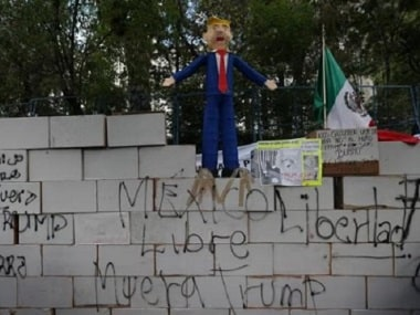 A symbolic wall and a pinata representing US President Donald Trump is seen during a protest outside the US embassy, in Mexico City. Reuters