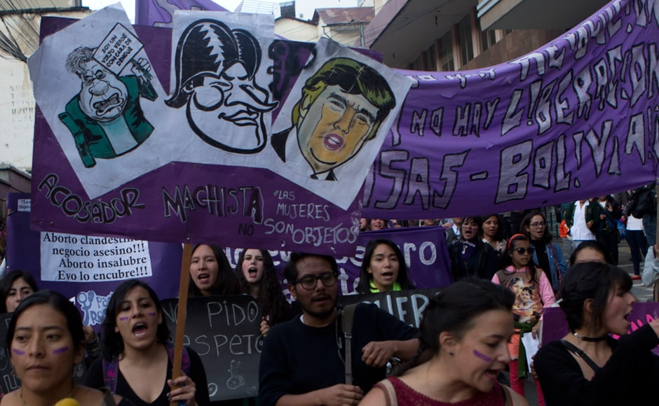 "A woman carries a sign showing images of US President Donald Trump, top right, and Bolivia's President Evo Morales, centre, over the Spanish words: ""Macho stalker"" during a protest against violence against women in La Paz, Bolivia on Wednesday. AP"