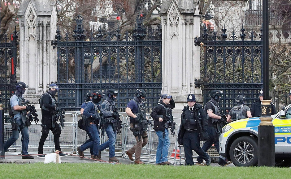 Armed police officers enter the Houses of Parliament in London after the House of Commons sitting was suspended as witnesses reported sounds like gunfire outside. AP